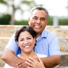 older couple smiling in front of brick wall