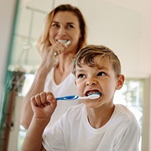 Mother and son brushing teeth together