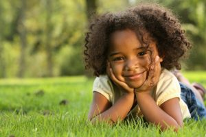 little girl smiling hands on face