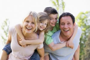 family of four hugging smiling