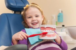child in dentist's chair pretending to brush teeth mold