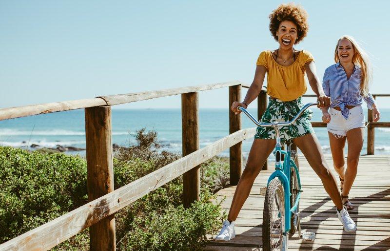girl biking on boardwalk during summer vacation